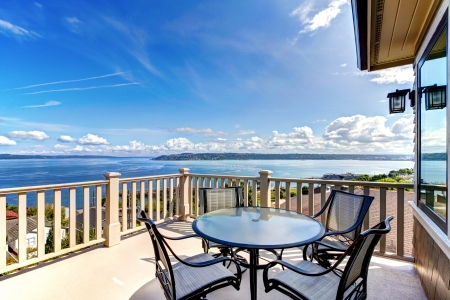 Luxury home balcony deck with water view and table with house. Stock Photo - 14874125