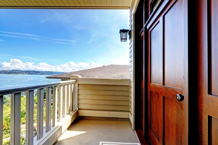 Front luxury wood door with water view and covered entrance. Stock Photo - 14859901