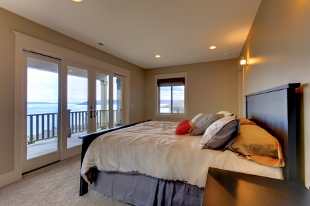Bedroom with water view, queen bed and beige walls.  Stock Photo - 14874086