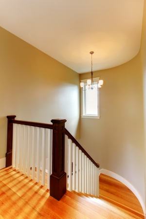 Beautiful hallway staircase with hardwood floor and round beige wall. Stock Photo - 14874084