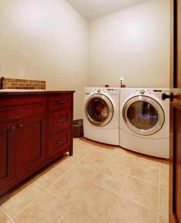 appliances: Simple new laundry room with new washer and dryer and wood cabinet.