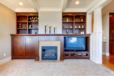 fireplace family: TV and entertainment center with white wood ceiling in a luxury room. Stock Photo
