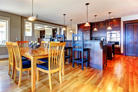 Luxury home kitchen and dining room with open floor plan and rich wood. photo