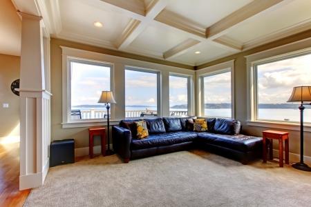 blue leather sofa: Soggiorno di lusso casa con tante finestre e divano blu.
