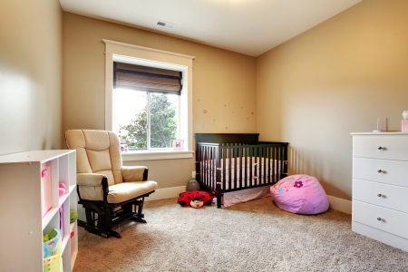 bedrooms: Nursing room for baby girl with brown wood crib and beige walls.