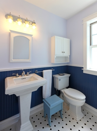 bathroom tile: Bathroom with sink and toilet with blue walls and tile floor.