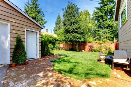 Fenced Backyard with house and garage and two doors Stock Photo - 14874132