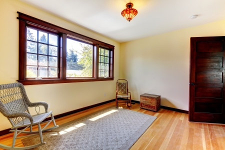 wood window: Nice empty room with chair, open door  and hardwod floor.
