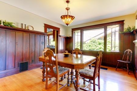 dining table and chairs: Nice dining room with wood walls and hardwood floor in an old house.