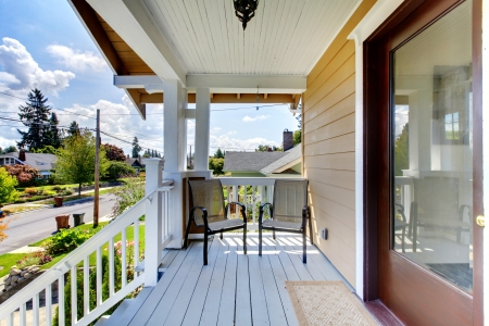 Front door entrance with steps and two chairs under covered porch. Stock Photo - 14874124