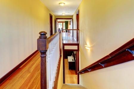 second floor: Yellow walls with stairway, hardwood floor and wood railing. Stock Photo
