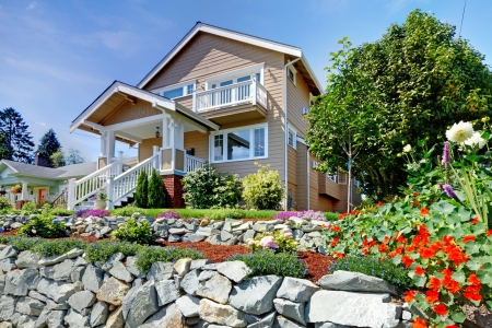 Two story beige nice house on the hill with rock walls and flowers. photo