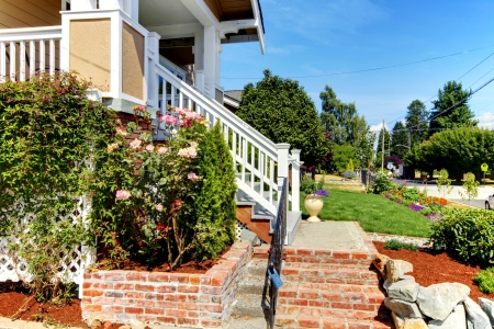 Nice house enrance with brick stairs, roses and stree view. Stock Photo - 14874131