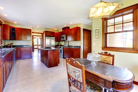 Large chery wood kitchen with dining room table and tile floor. photo