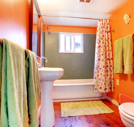 Orange and green bathroom with tub, sink  and wood floor  photo