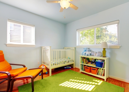 baby on chair: Baby nursery room design with green rug, blue walls and orange chair.