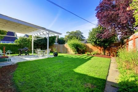 Achtertuin met groene gras hek en het huis overdekt terras. Stockfoto