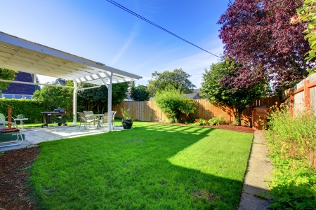 Backyard with  green grass  fence and house covered deck. photo