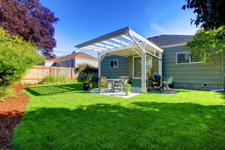 Green small house with porch and backyard with fence. Stock Photo - 14968403