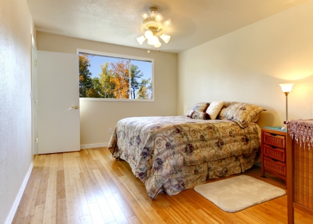 apartment: Simple bedroom with hardwood floor and fall window view and flowery bedding. Stock Photo