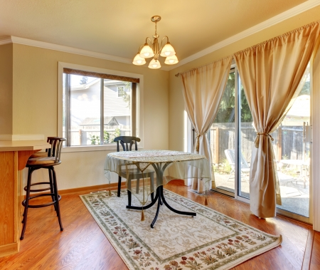 Dining room area with doors and window and simple round table and hardwood floor. photo