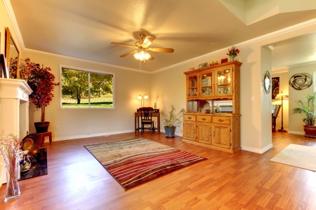Large Living room with hardwood floor, red rug  and beige walls. photo
