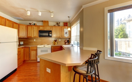 Simple standart American wood  kitchen with hardwood floor and chairs. photo