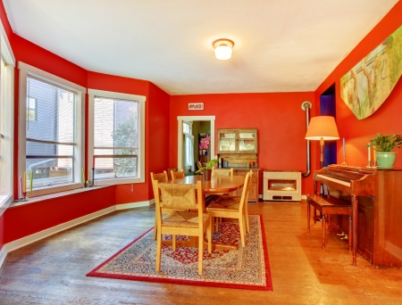 Red dining room with piano, hardwood floor and many windows  Stock Photo
