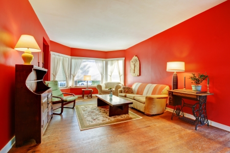 antique chair: Large red living room with hardwood and antique furniture with lamps  Stock Photo