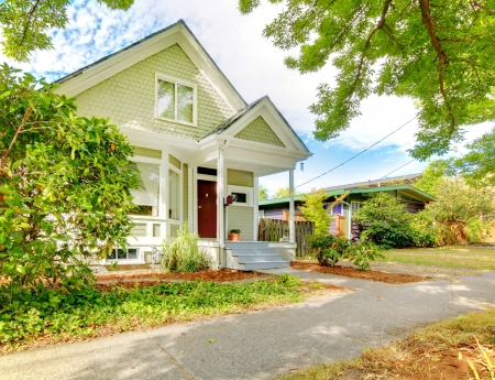 Small cute craftsman American house wth green and white and red door  Standard-Bild
