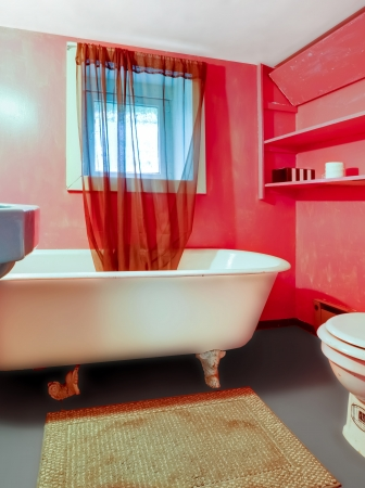 Red pink bathroom with white antique tub and curtain and rug  photo