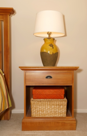 nightstand: Wood furniture nightstand with lamp and bed.