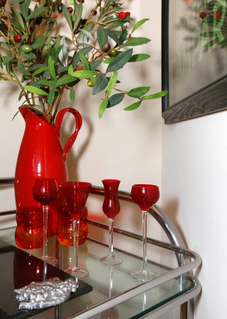 glases:  Cart with red glasses and vase with olives. House details. Stock Photo