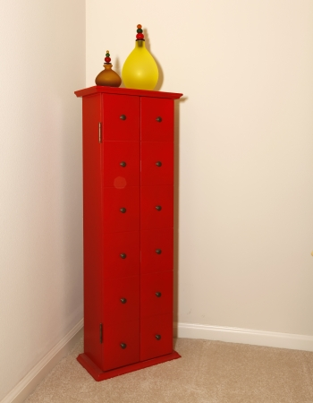 Corner with red tower modern dresser furniture with glass vases. Stock Photo