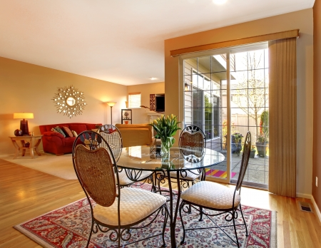 Elegant dining table near large door and living room. photo