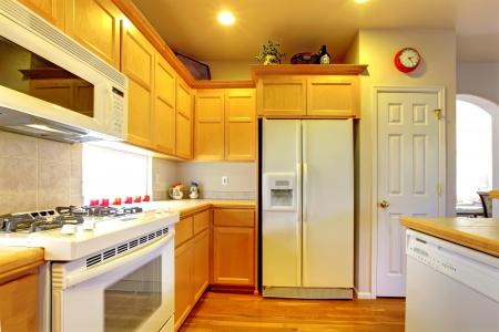 kitchen counter top: Kitchen with yellow wood cabinets and white appliances and hardwood floors. Stock Photo