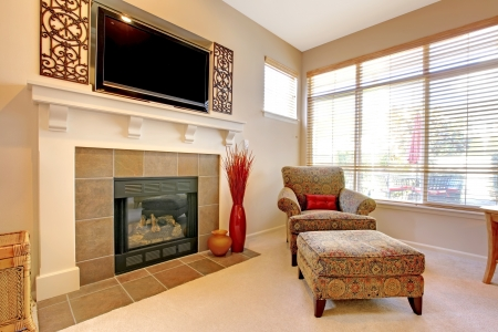 Fireplace with large TV above, elegant chair with windows. Stock Photo