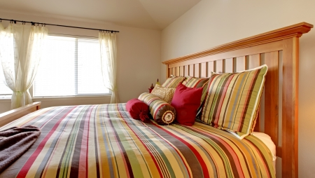 Large bed with beautiful bedding in stripe red, yellow and green. Stock Photo - 15783859