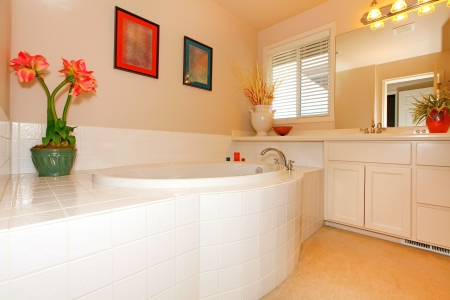 double sink: Bathroom with large round white tub and cabinets with  double sink.
