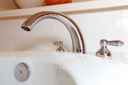 Tub fawcet details with white tiles on the back. Reklamní fotografie