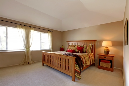 stipe: Lagre bedroom with wood bed and nightstand with stipe red, green and yellow bedding.
