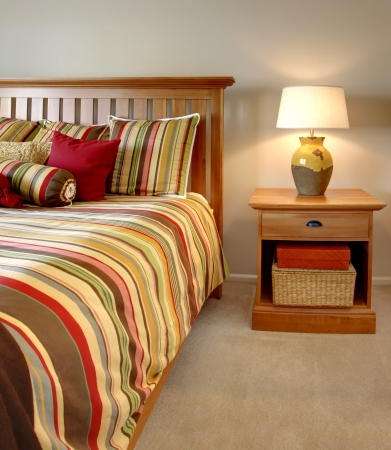 nightstand: Wood bed and nightstand with stripes in red, yellow and green with beige carpet. Stock Photo