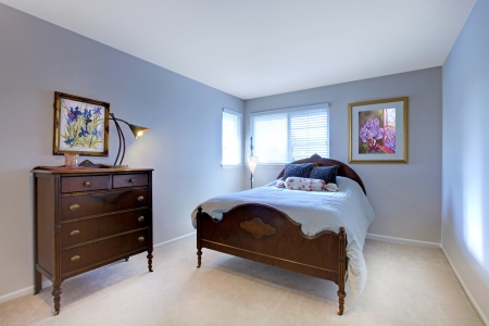 Blue bedroom with dark wood bed and dresser and beige carpet. Stock Photo - 15783869