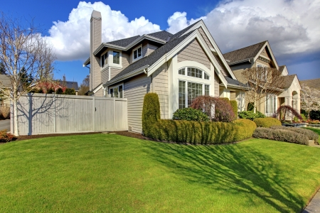 Classic American house with fence and green grass during spring. photo