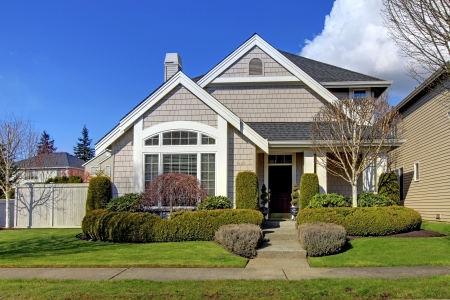 Classic new beige American house exterior in the spring.