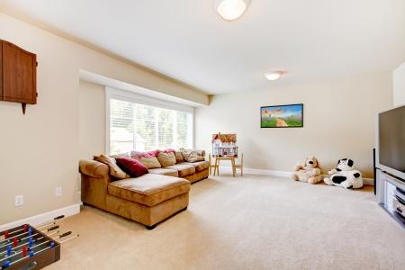 Salle de jeux TV de séjour avec canapé marron large avec des jouets. Banque d'images - 15959936