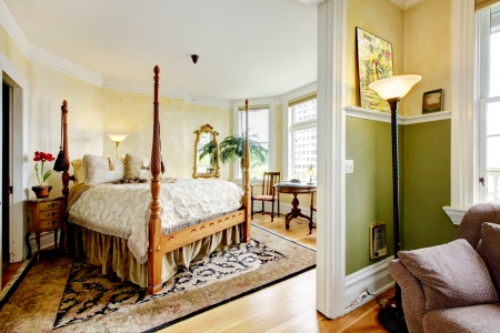 15960581: Large historical Inn room interior - bedroom with antique post bed.