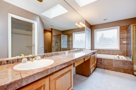 Large lnew uxury bathroom with red granite countertops and tub.