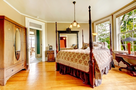 old furniture: Large historical Inn room interior - bedroom with antique post bed.
