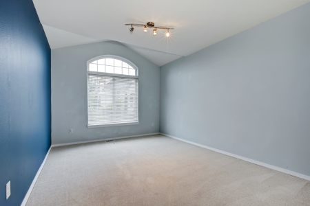 Blue large empty room with carpet and vaulted ceiling with huge window. Stock Photo